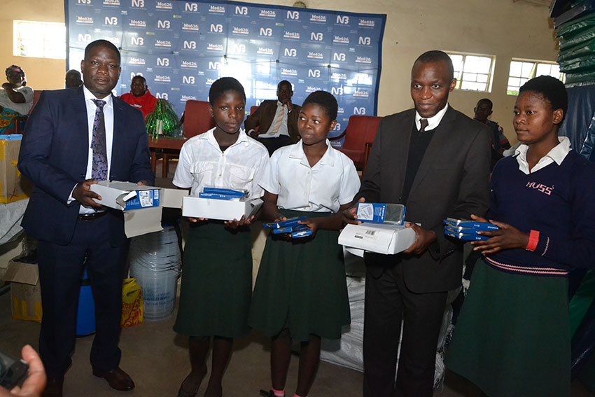 Jiya (left) presenting some educational materials to Namikasi Secondary School girls together with NBM Head of Card and eBanking William Kaunda (second right)